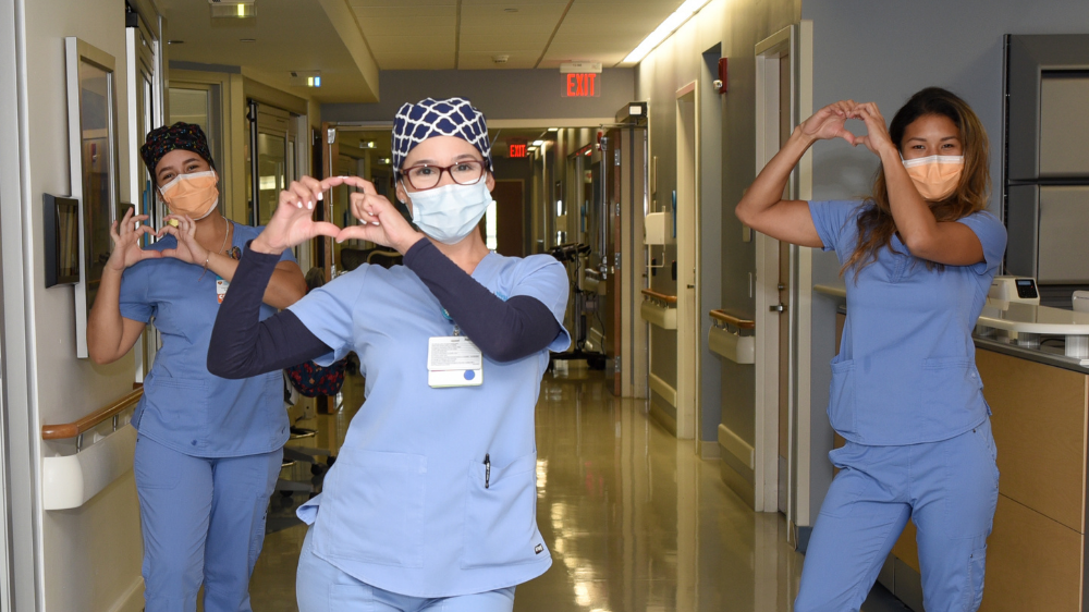 nurse practitioner wearing a face mask and making a heart shape with her hands