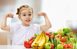 Child with fruits and veggies and flexing muscles